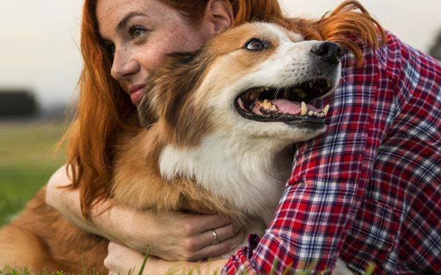 fotografie ženy objímající psa v praku