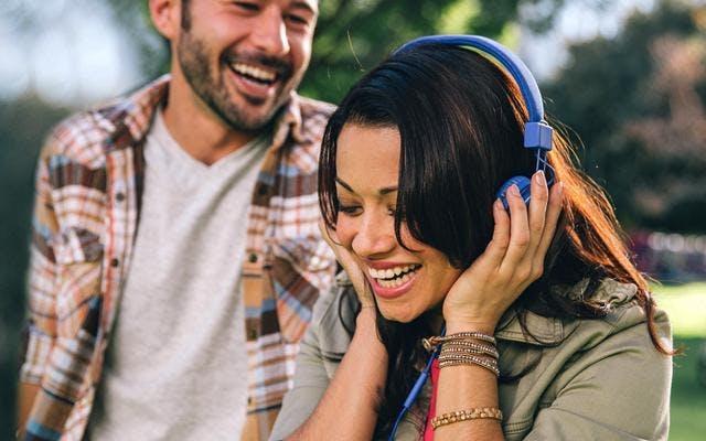 fotografie muže a ženy poslouchající hudbu