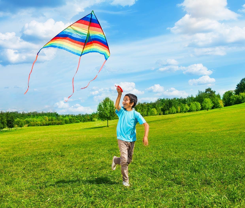 أم مستلقية على العشب وتحمل ابنتها في الهواء كالطائرة، الطفلة تبتسم