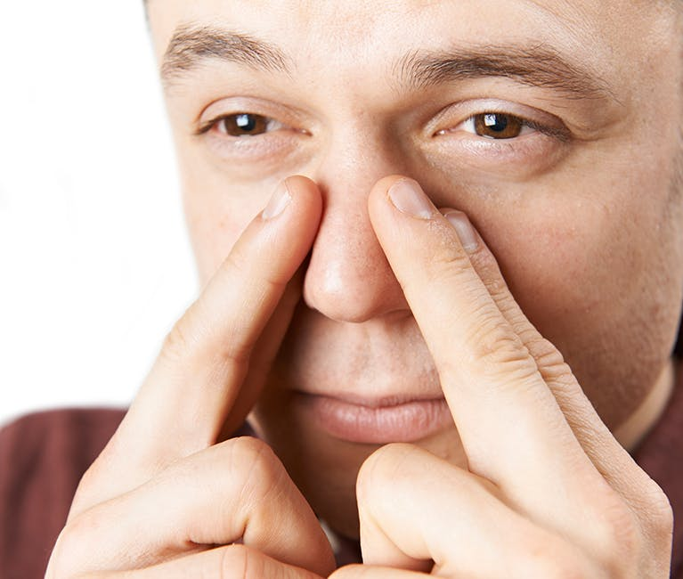 Man suffering nasal congestion massages his sinuses