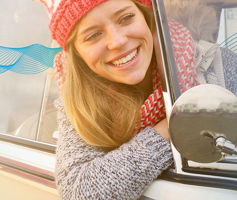 Frau, die ihren Kopft aus dem Autofenster hält und lächelt