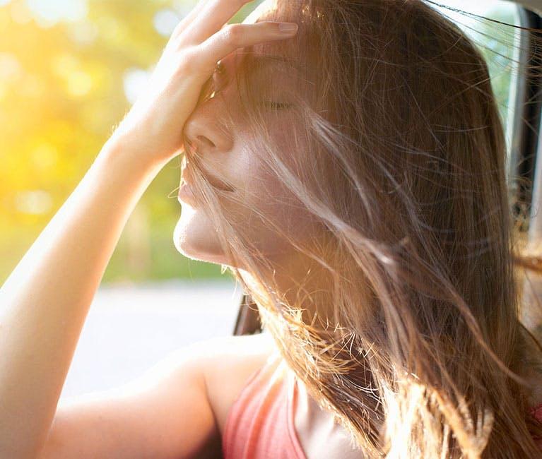 Frau in Auto streckt ihren Kopf aus dem Fenster und streicht sich die Haare aus dem Gesicht