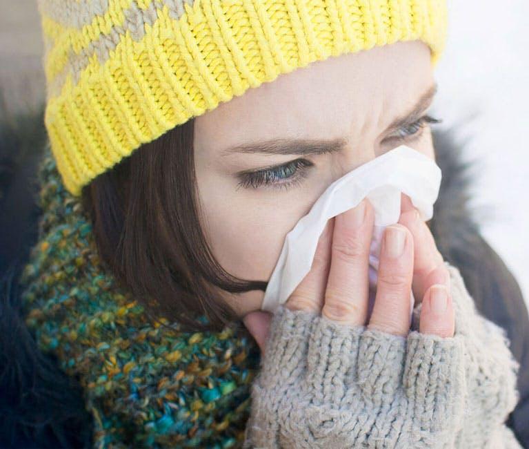 Frau in Winterkleidung putzt sich die Nase