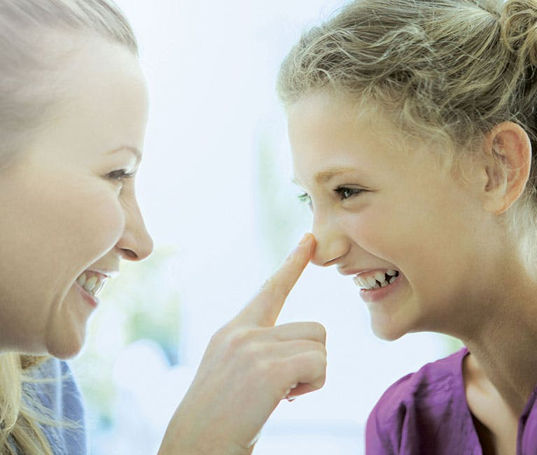 Eine Mutter berührt die Nase ihrer Tochter
