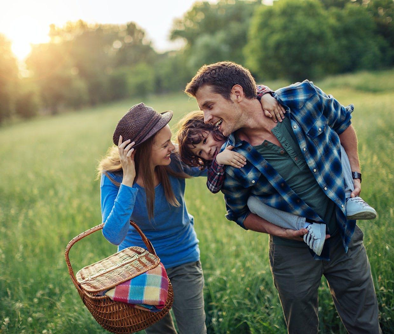 Eine junge Familie ohne Heuschnupfen genießt die Natur dank der Hilfe von Otri Allergie Nasenspray.