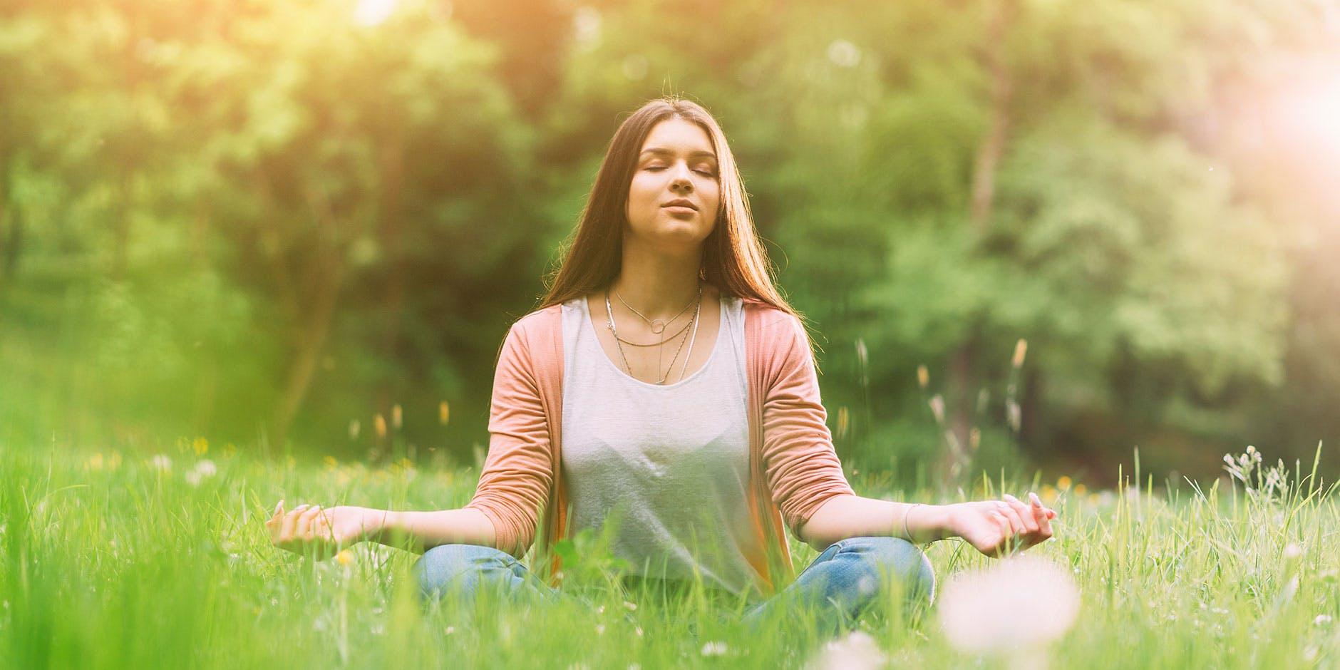 Eine junge Frau sitzt in einem Feld dank der Therapie mit einem Heuschnupfenmittel.