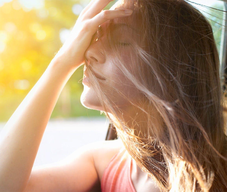 Verstopfte Nase befreien: Eine Frau sprüht Nasenspray
