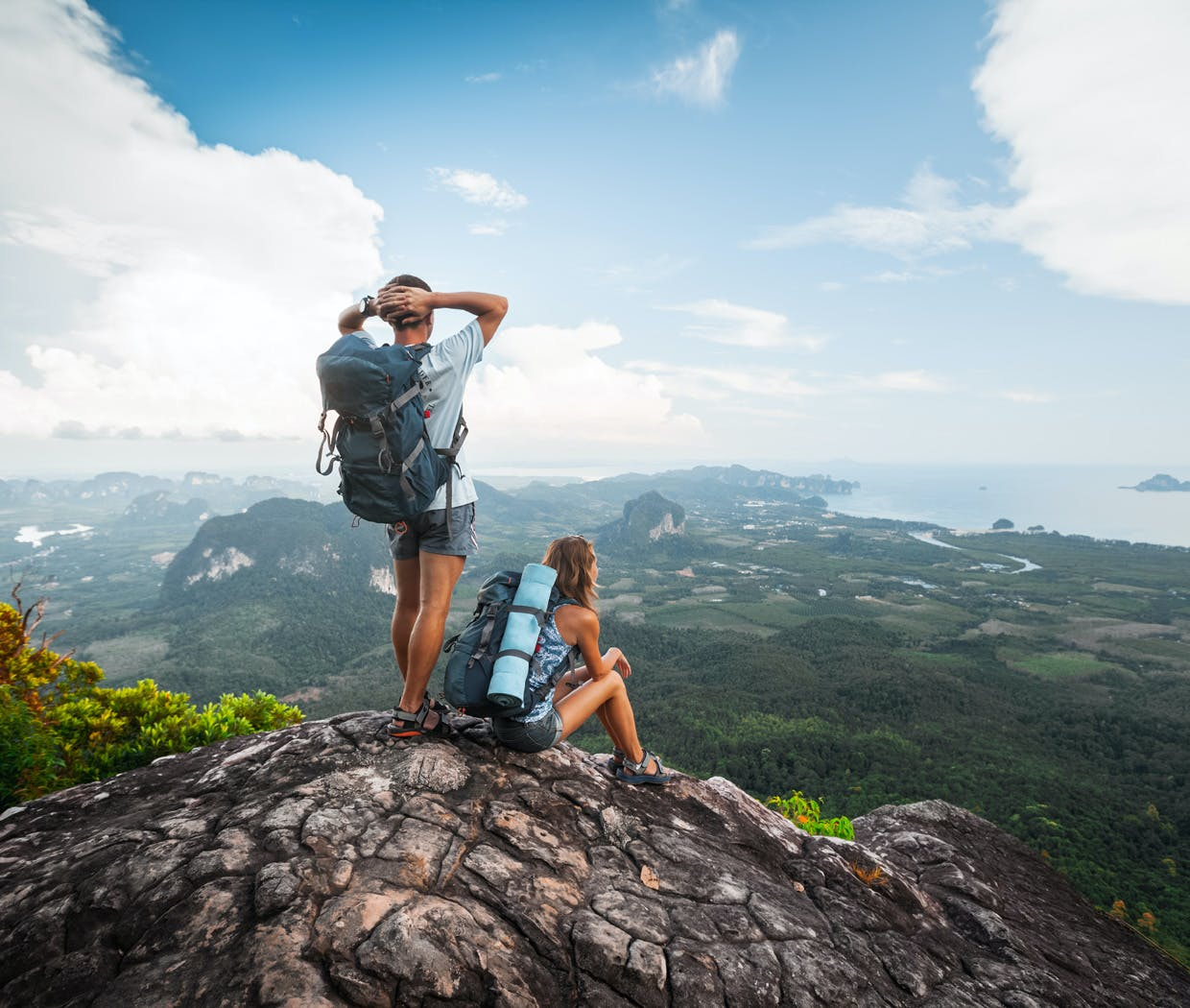 Man and woman stand on top of rock cliff as they gaze into the horizon