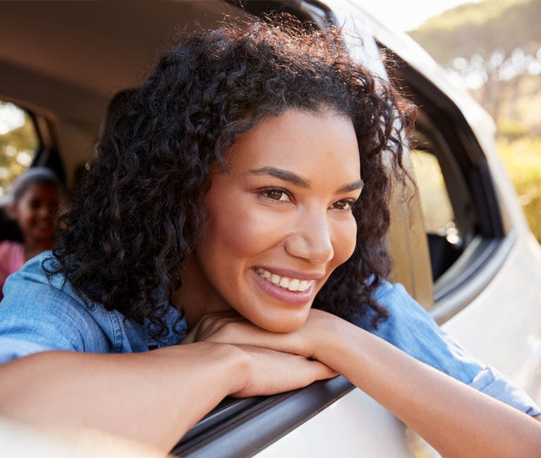 Woman enjoying being free from a cold, blocked nose and hay fever in a car with the window open