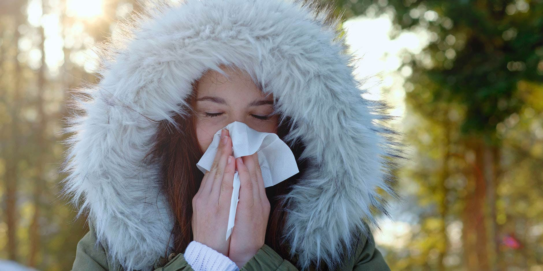 Woman is blowing her congested nose in the cold winter air.