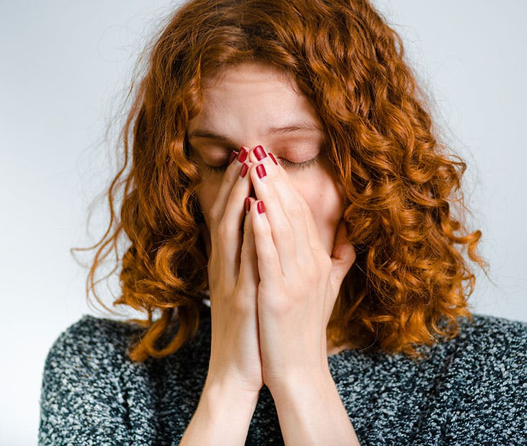 A long-haired woman has both hands over her nose and mouth and tries to cough