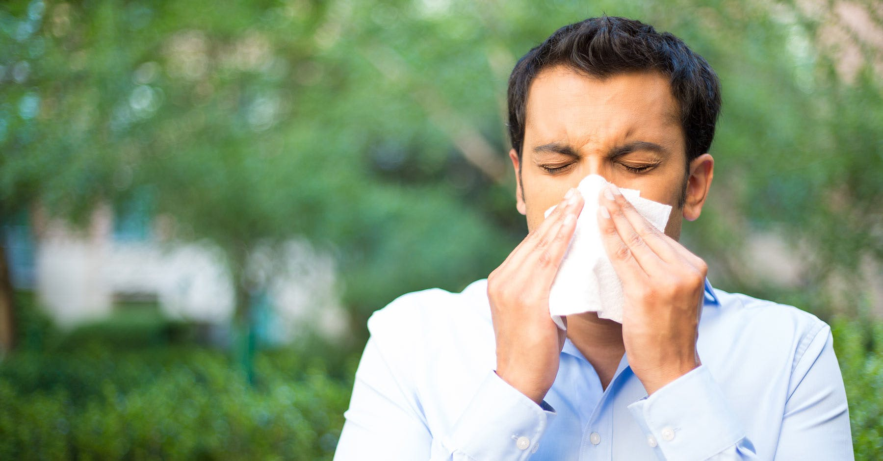 A black-haired man in a blue shirt is trying to blow his nose in a tissue