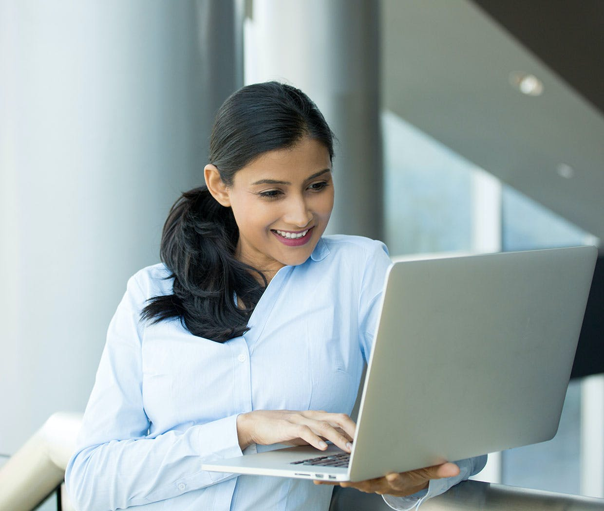 An office environment with woman sitting at laptop writing notes
