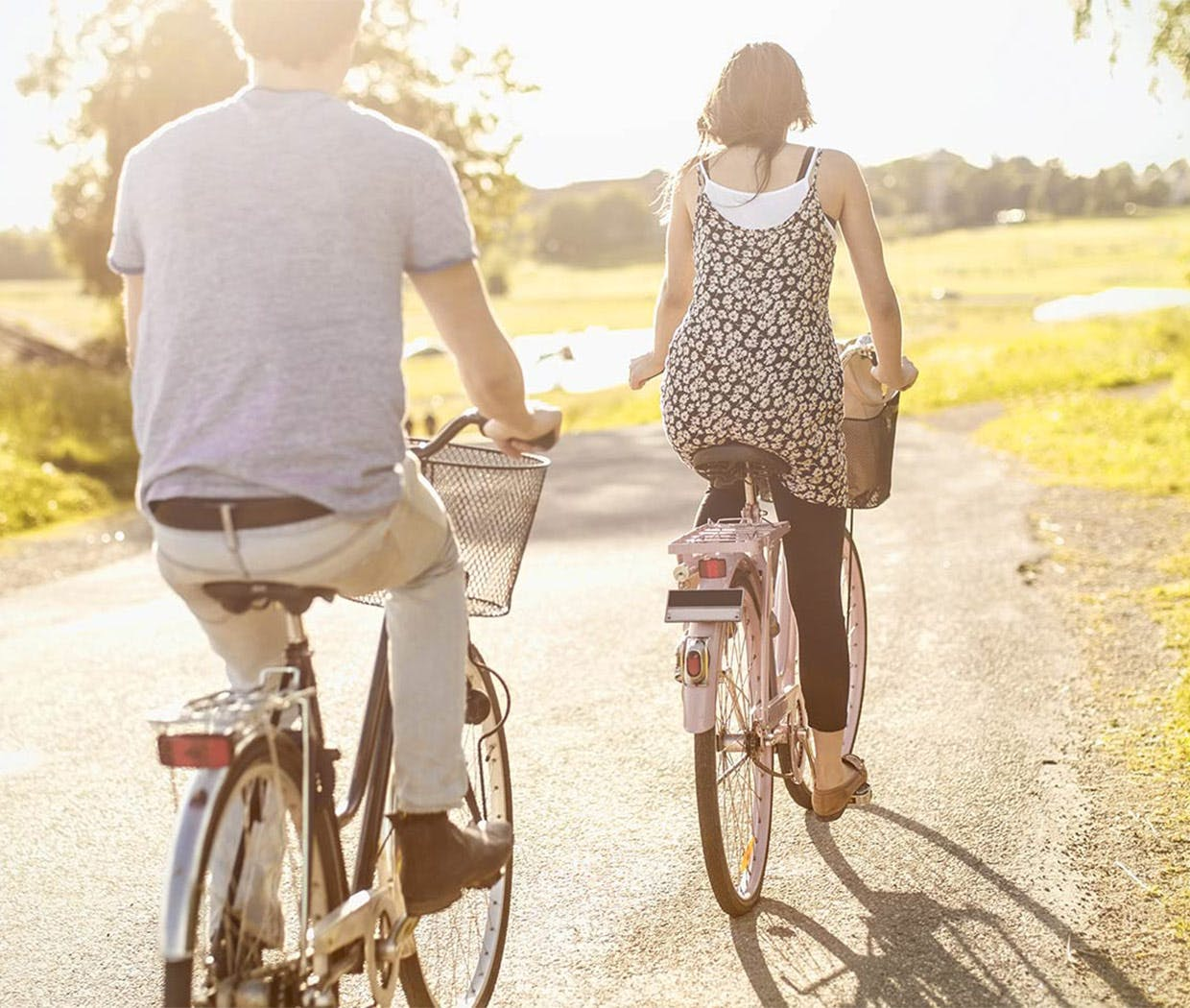 Couple riding bicycles in the countryside in summertime