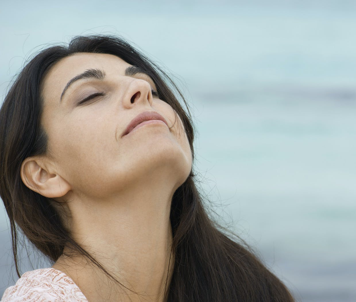 Woman with clear sinuses lifts head to breath in fresh air