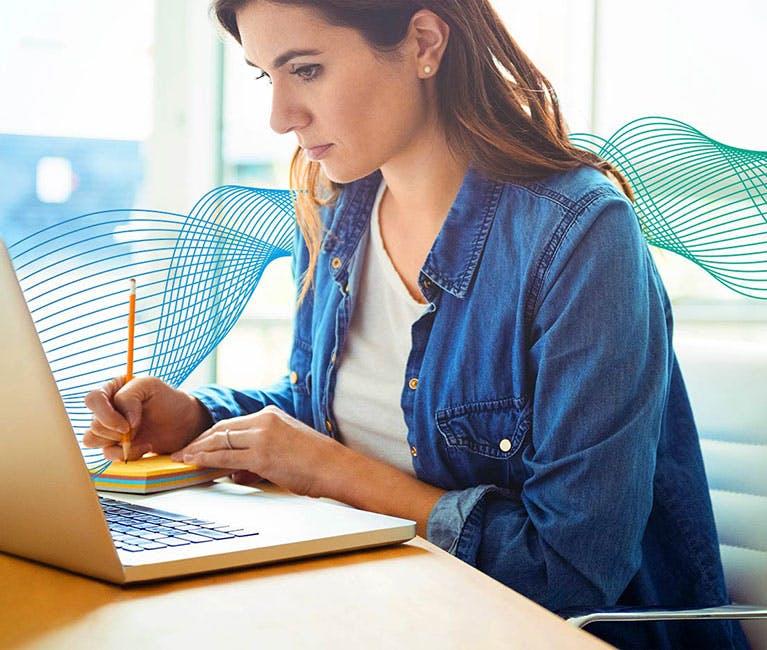 Cadre d'un environnement de bureau avec une femme prenant des notes assise à un ordinateur portable