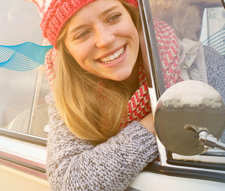 Kvinne smiler med hodet ut av bilvinduet