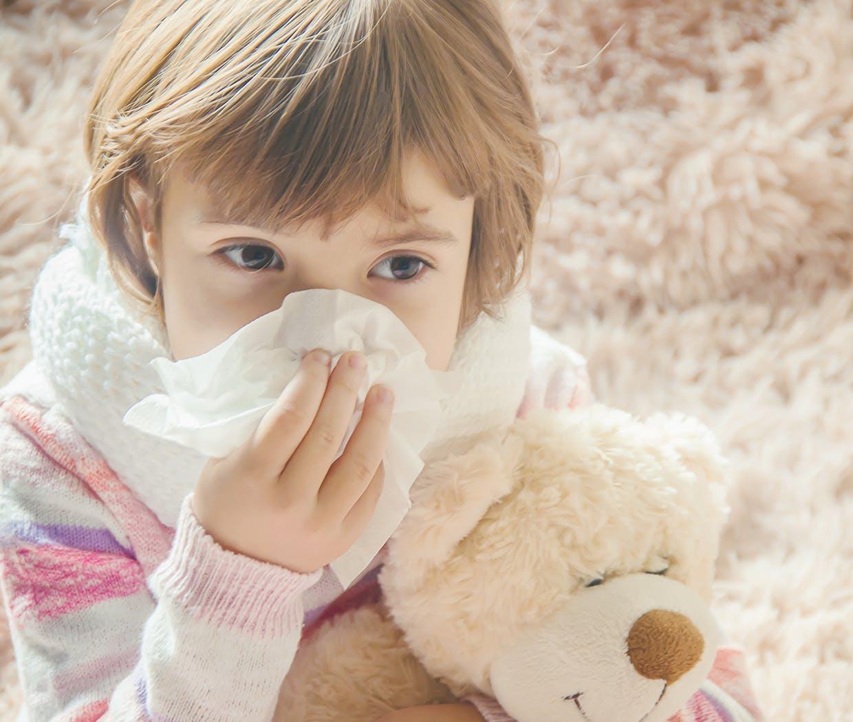 Copil cu ursuleț de pluș în brațe și care își suflă nasul
