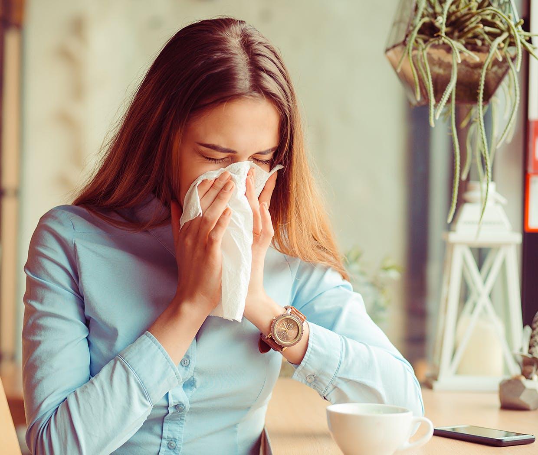 Femeie care își suflă nasul