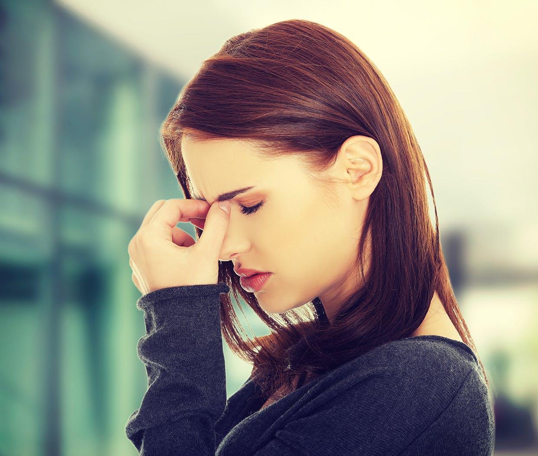Femeie care își apasă sinusurile