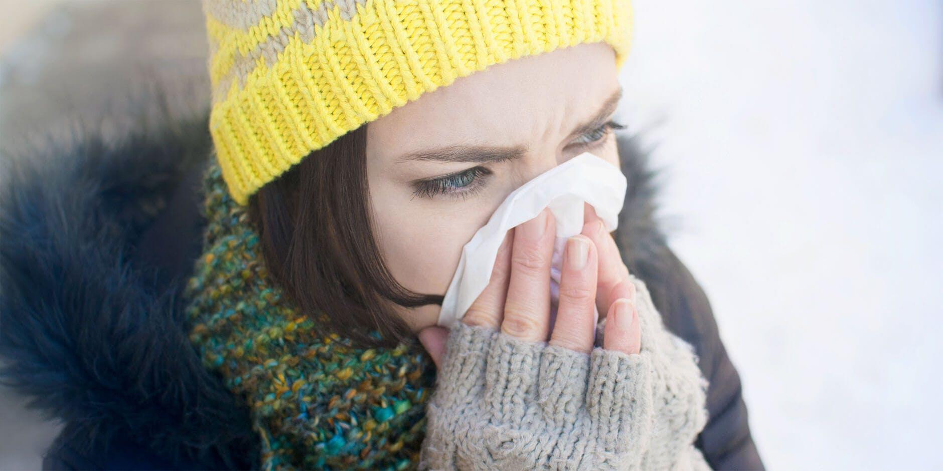 Женщина, одетая в зимнюю одежду, сморкается