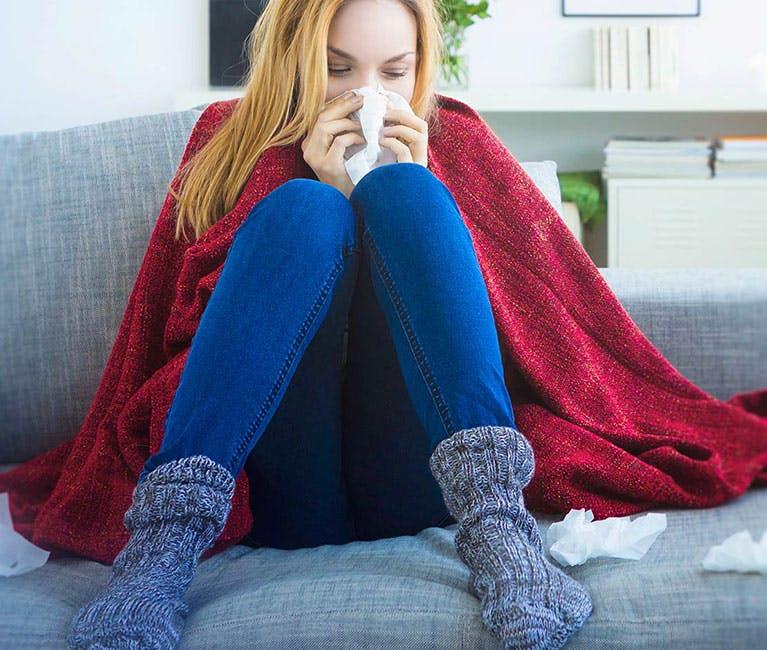 Женщина дома на диване, укрытая одеялом, сморкает нос