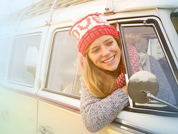 Женщина улыбается высунув голову из окна автомобиля
