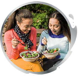 Two women having a snack outdoors
