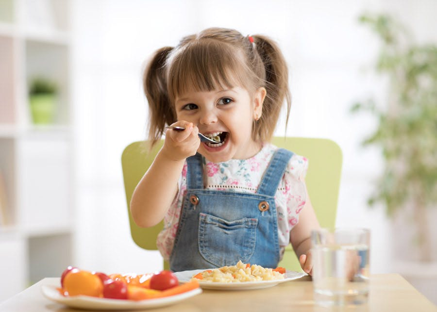 Toddler girl eating vegetables in a high chair