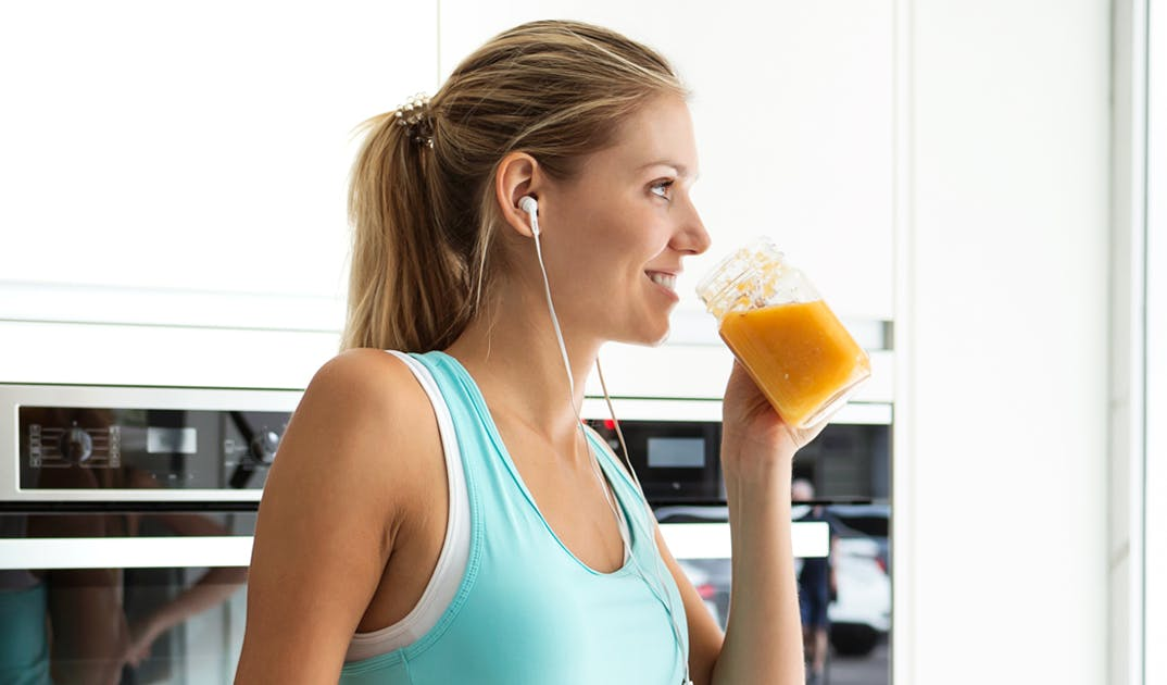 blonde woman listening to music while drinking an orange smoothie