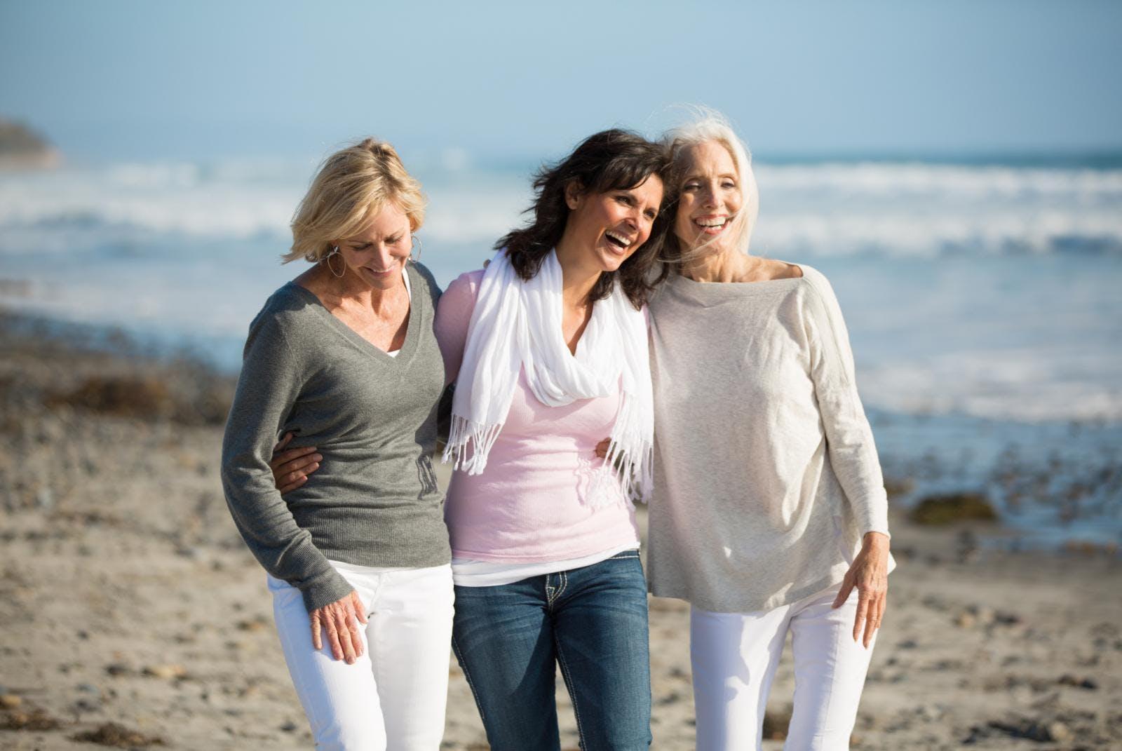 Three elderly ladies walking on the beach.