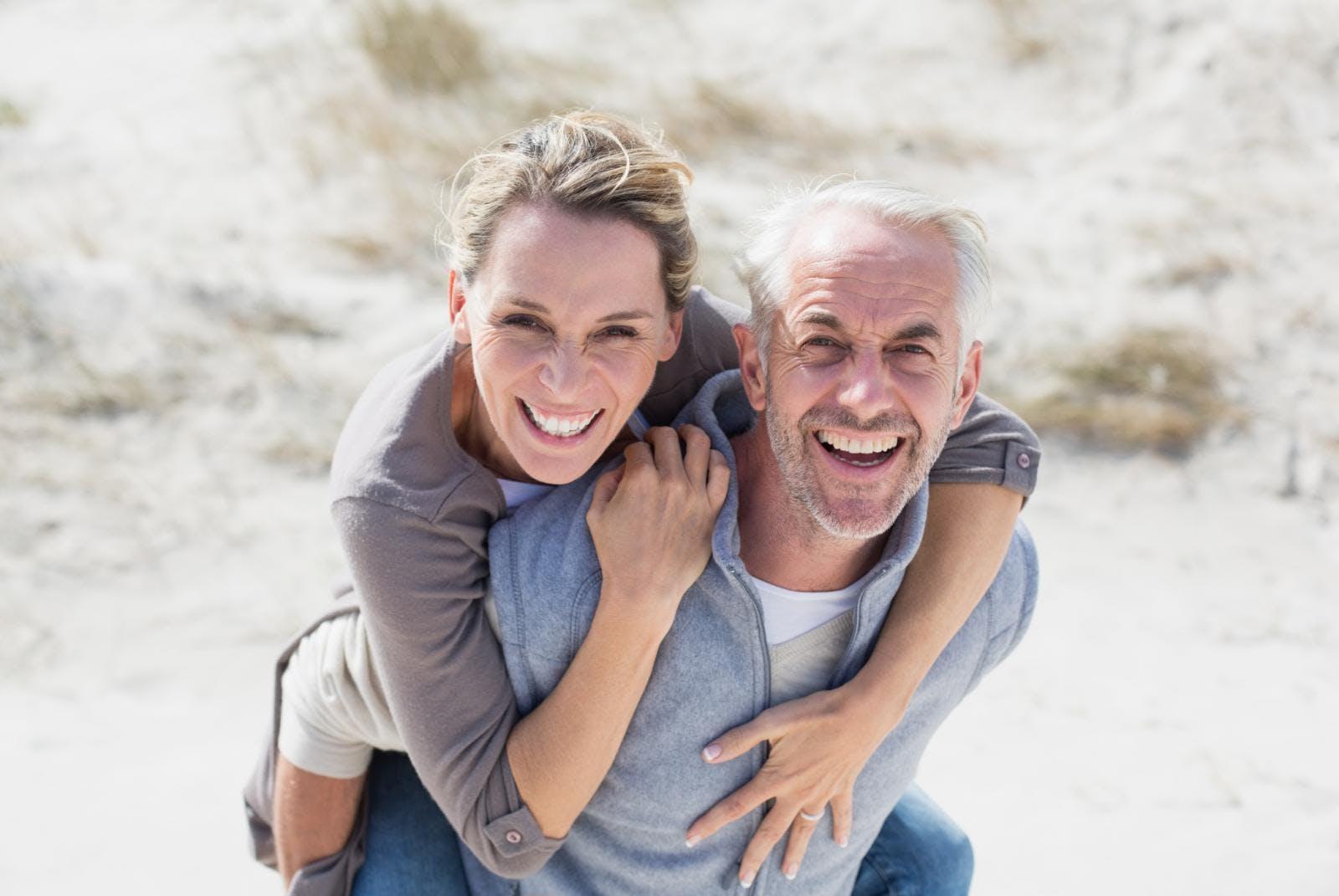 Elderly man giving a woman a piggyback ride on the beach.