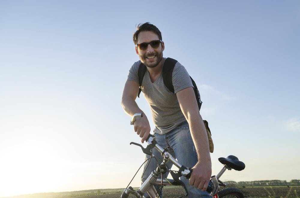 Guy with bike in front of sun