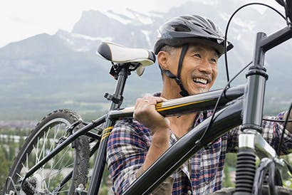 Smiling older man with helmet carrying his bicycle.