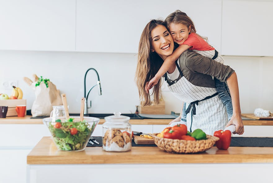 Frau steht lachend in der Küche und hat kleines Mädchen auf dem Rücken.