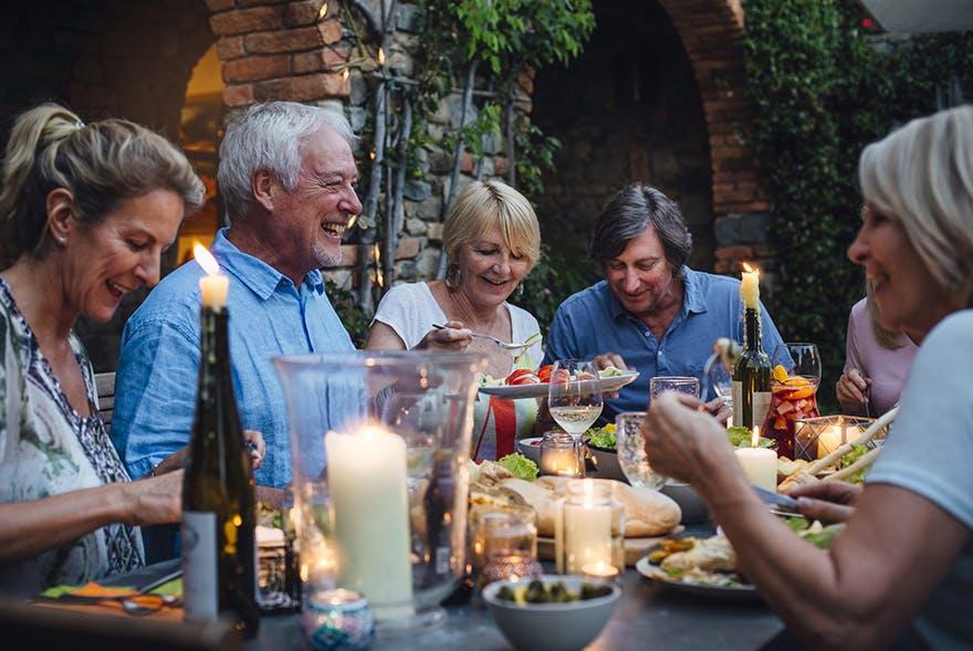 Gruppe älterer Leute sitzt am Tisch zum Essen zusammen.