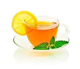 Chai a L'orange tea drink in a clear teacup with a lemon wedge and mint sprig