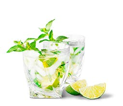 Mint Lime Refresher drink in high ball glass with lime wedges
