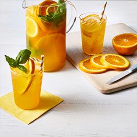 Pitcher and glasses filled with Orange Basil Sparkler drink beside slices of fresh orange