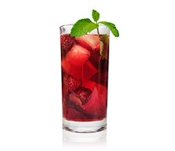 Rock Your World purple drink in glass with ice cubes and a mint garnish