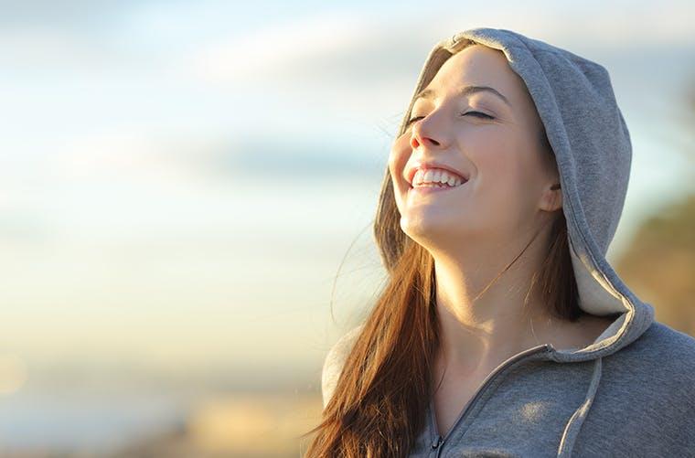 Woman in hooded sweatshirt smiling outdoors