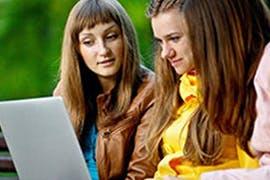 three women looking at laptop