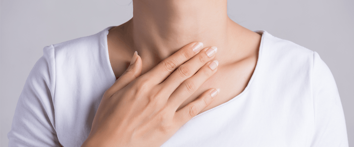 woman in white touching her chest with grey background
