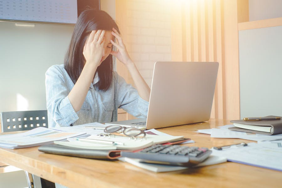 Stressed woman sitting at desk in front of laptop with head in her hands