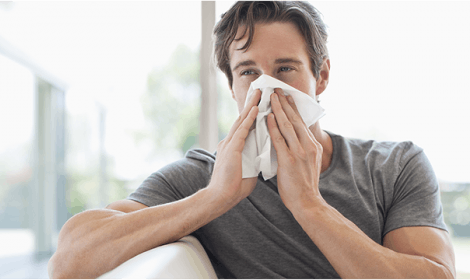 Man blowing nose into a tissue