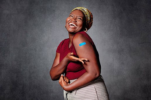 A woman laughing gesturing to the bandaid on her arm