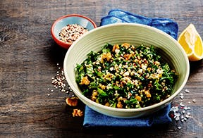 A bowl of kale salad with mixed grains and nuts sits on a table with a blue napkin, there is a lemon off to the right hand side