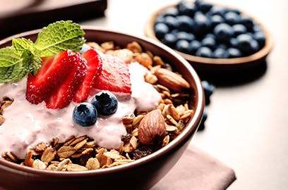 A bowl of yoghurt with strawberries, blueberries and nuts with a sprig of mint sits on a surface, there is a bowl of blueberries in the background