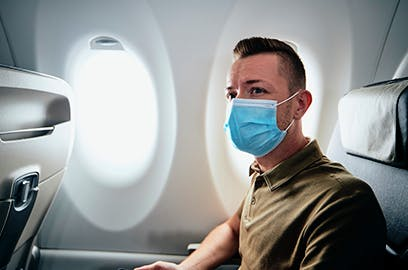 A man sitting on an airplane is wearing a mask