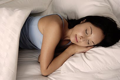 A woman is lying in bed, asleep.